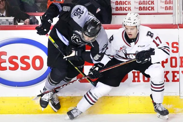 Calgary Hitmen defenseman Jackson van de Leest (left) battling for the puck during Western Hockey League action against Red Deer in January 2020.