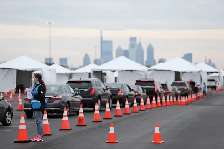 Philadelphia Medical Reserve Corps volunteer Emma Ewing, a sophomore at Temple University, directs cars at the city's coronavirus testing site next to Citizens Bank Park in South Philadelphia on Friday, March 20, 2020.