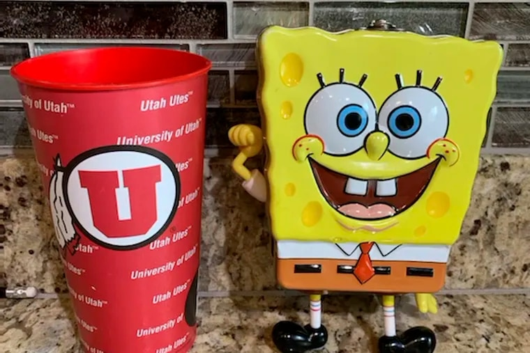 In this photo provided by Utah sports writer Andy Larsen are a childhood piggybank, right, and a plastic cup on Tuesday, Nov. 24, 2020, in Salt Lake City. Larsen's spontaneous tweet looking for someone in need to whom he could give the $165 he had in the two items quickly snowballed into tens of thousands of dollars in donations from strangers, as well as messages from people who could use the help. (Andy Larsen via AP)