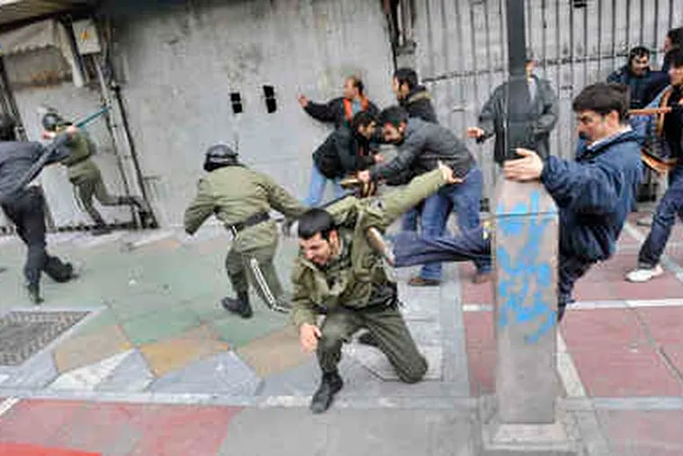 This photo, taken by an individual not employed by the Associated Press and obtained by the AP outside Iran, shows protesters beating police officers during protests in Tehran yesterday.