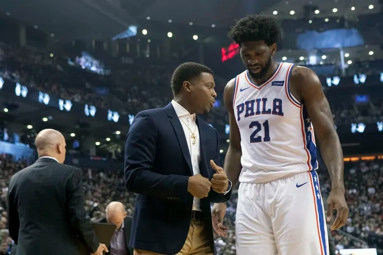 Joel Embiid (21) talks to injured Raptor Kyle Lowry after his scoreless outing.
