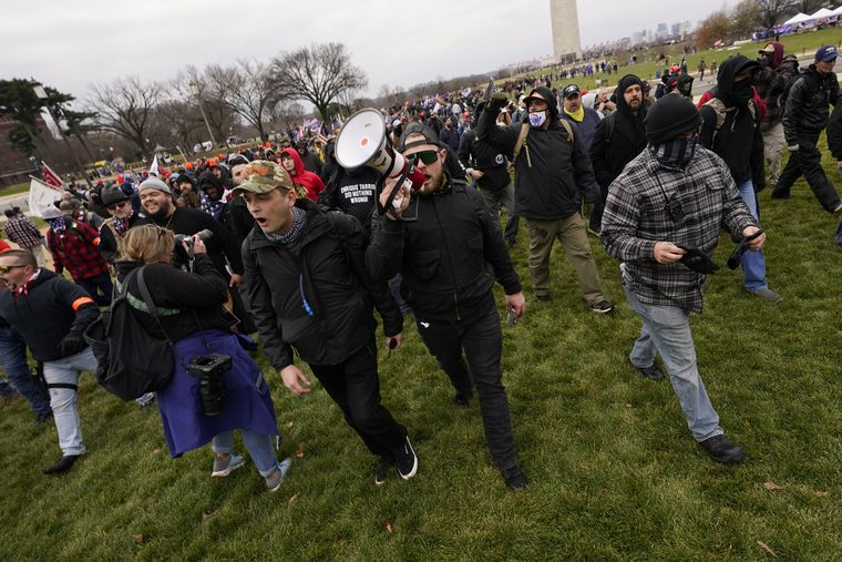 Proud Boys leaders Zach Rehl, of Philadelphia (camouflage hat, left), Ethan Nordean, of Seattle, and Joe Biggs, of Florida, (grey plaid flannel with neck gaiter) lead marchers to the U.S. Capitol on Jan. 6. Nordean and Biggs have both been charged with playing a role in the storming of the Capitol.