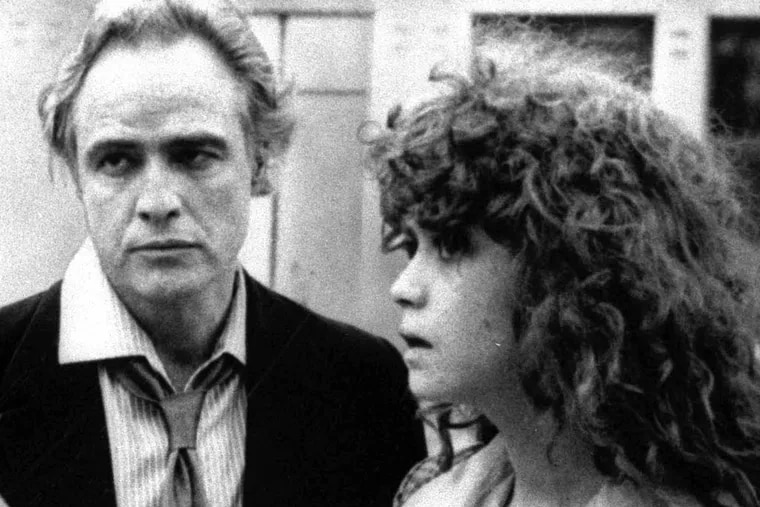 """Director Bernardo Bertolucci, left, discusses a scene from """"Last Tango in Paris"""" with leading actor Marlon Brando and actress Maria Schneider during location shooting in Paris in this undated black and white photo."""