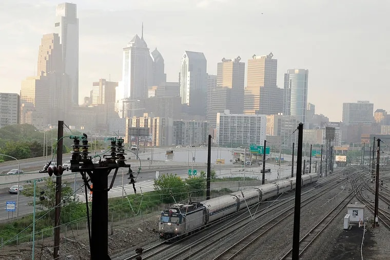 An Amtrak train heads north from 30th Street Station. Plans call for partially capping over the rail yard and installing pedestrian bridges and other amenities.
