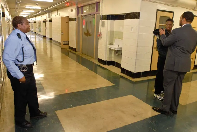 A School District police officer watches as South Philadelphia High School Principal Otis Hackney questions a student for being in the restroom without a hall pass between classes.