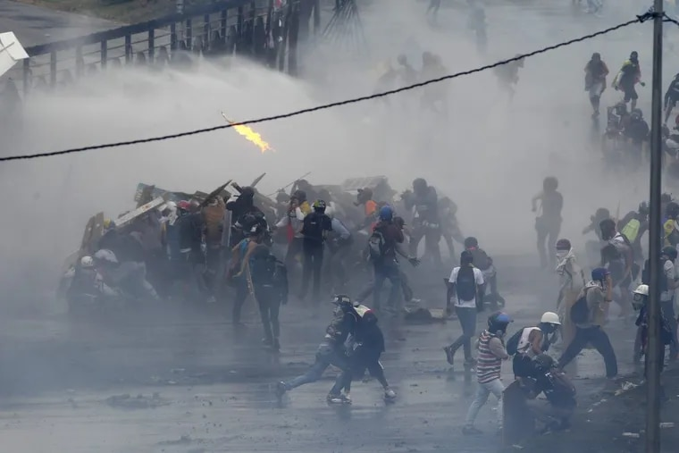 Demonstrators clashing with authorities on the fence of an air base in Caracas, Venezuela, in June.