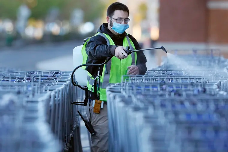 A worker sprays shopping carts with sanitizer at the Sam's Club in Deptford.
