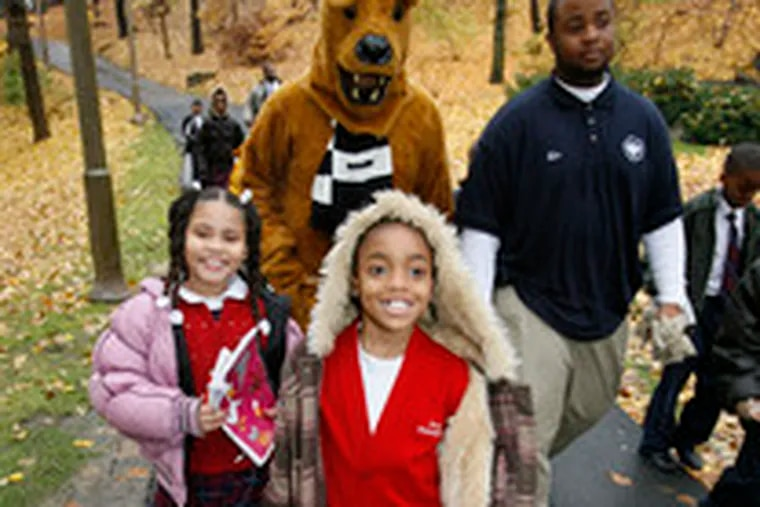 Accompanied by the Nittany Lion, Nachae Collins (center) and fellow third-graders at First Philadelphia Charter School tour the campus of Penn State Abington.