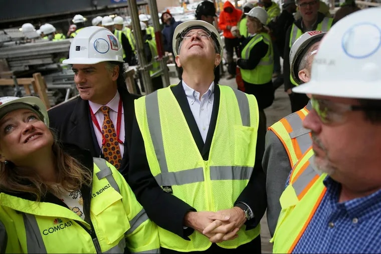 From left, Karen Buchholz, Comcast Corp., senior vice president of administration; John Gattuso, regional director and senior vice president of Liberty Property Trust, and Comcast CEO Brian Roberts watch as the final beam is raised at the new Comcast tower on Wednesday.