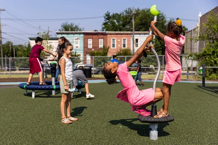 Alani Falcon, 2nd grader at Coopers Poynte Family School, (left), watches fellow students Envy Custis, 2nd grader, (center), and Aniya Custis, 1st grader, (right), play in the park at Dominick Andujar Park in Camden on Tuesday.