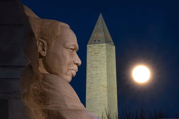 The rising full moon passes behind the Martin Luther King Jr. Memorial and the Washington Monument on Dec. 29.