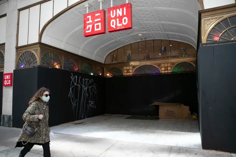 A pedestrian walks by a boarded-up Uniqlo store at 16th and Chestnut Streets in Center City Philadelphia last week.