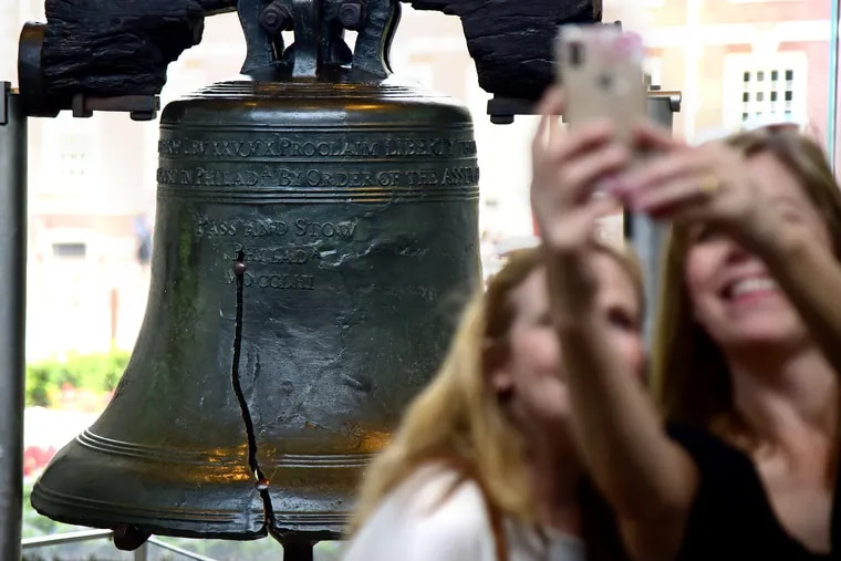 Tourists visit and take selfies in front of the Liberty Bell.