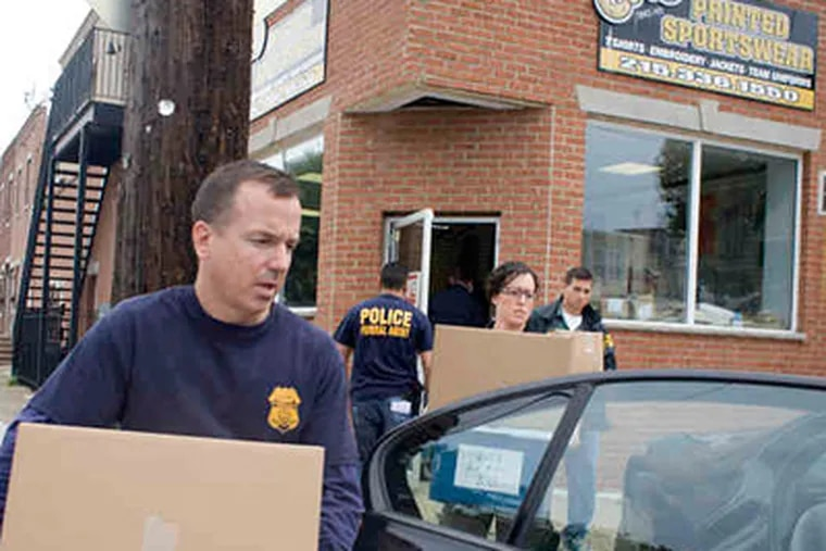 Federal agents remove material from KO Sporting Goods, also called KO Printed Sportswear, in South Philadelphia. (Ed Hille / Staff Photographer)