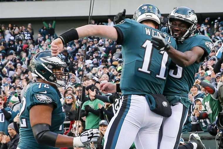 Eagles wide receiver Nelson Agholor (right) celebrates his touchdown with Eagles quarterback Carson Wentz and offensive lineman Halapoulivaati Vaitai against the Chicago Bears on Sunday, Nov. 26, 2017.