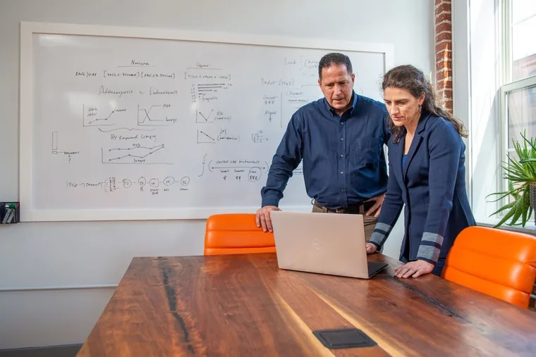 Partners Bob Scavilla and Kim Kalishek work at a handcrafted table created for their company, FourFront, by fuugs Woodworking of Philadelphia.