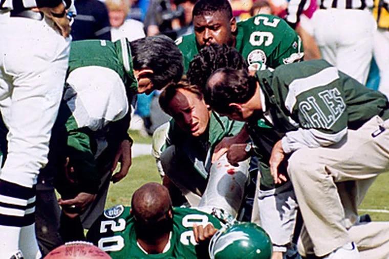 Philadelphia Eagles' defensive end Reggie White (92) looks on as Andre Waters (20) is tended to by team doctors in 1992. (AP Photo / Wilfredo Lee, file)