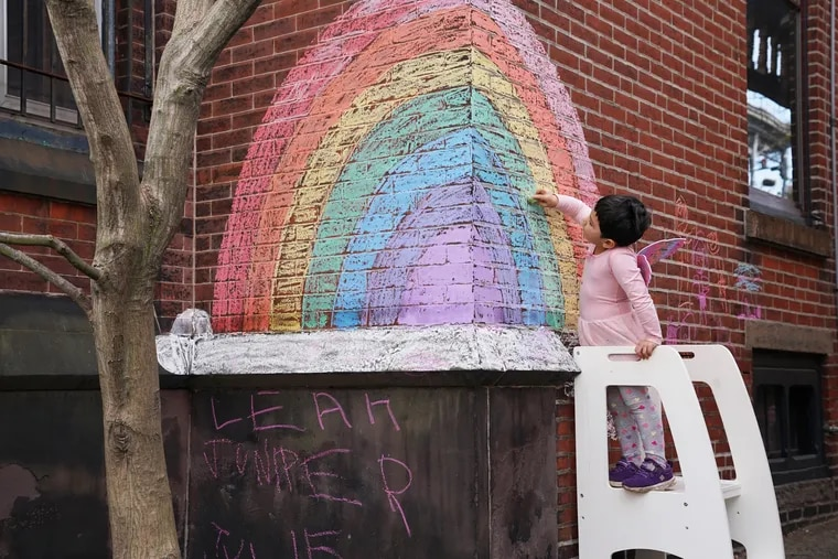 Four-year-old Juniper Assis Finlayson colors in blank spots with chalk on a rainbow she and her Mom drew earlier in the week on Tuesday, in Philadelphia, March 27, 2020. Juniper also enjoys going for walks with her mom's and participating in the rainbow scavenger hunt around 26th and Poplar Streets.