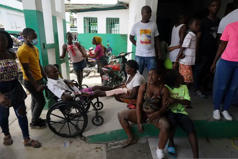 People injured in a car accident, sitting right, wait with others injured during the earthquake for X-rays at the General Hospital in Les Cayes, Haiti, on Wednesday.