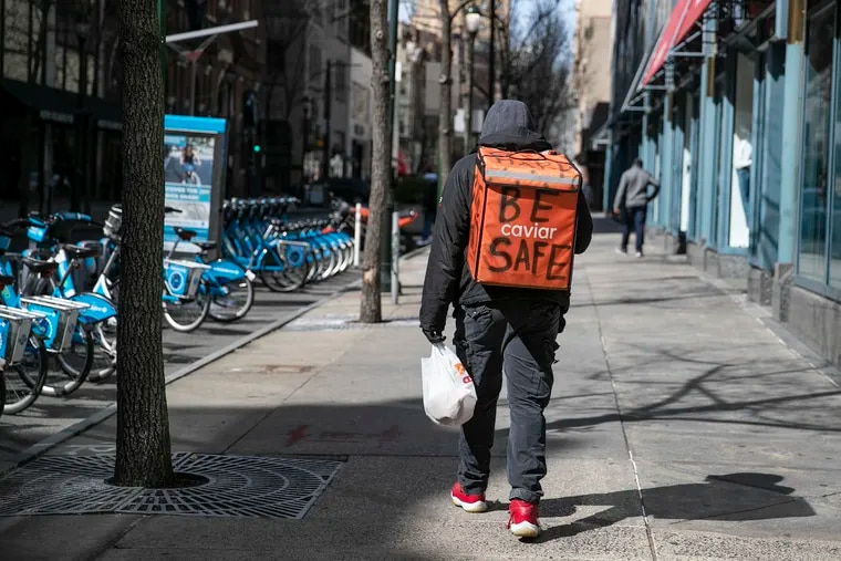 """A food delivery worker who did not want to give his name has """"Be Safe"""" written on his delivery backpack while walking down Chestnut Street in Center City Philadelphia on Wednesday, March 18, 2020. Gig workers, like Caviar couriers, do not get mandated paid sick leave in Philadelphia because they are independent contractors. A new bill seeks to change that."""