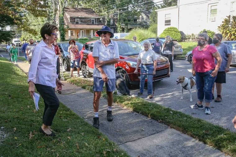 Virginia Maroun, left greets Al Campanile with other Lansdowne neighbors to celebrate his 37-year postal carrier career with a clap out at the last house on his route on Monday.