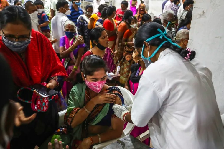 A health worker administers a dose of Covaxin as hundreds line up to receive their second dose of vaccine against the coronavirus at the municipal stadium in Hyderabad, India, Thursday, July 29, 2021.