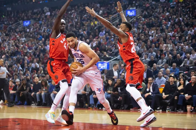 The 76ers' Ben Simmons drives between Toronto's Pascal Siakam, left, and Norman Powell during the first half.