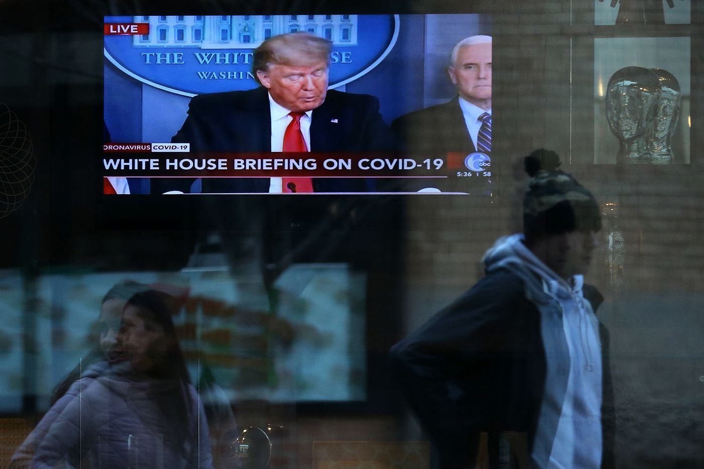 President Donald Trump is pictured on a television screen inside the Home2 Suites in Center City as he speaks during a coronavirus press briefing on Thursday. The U.S. on Thursday became the country with the most confirmed cases of the coronavirus.