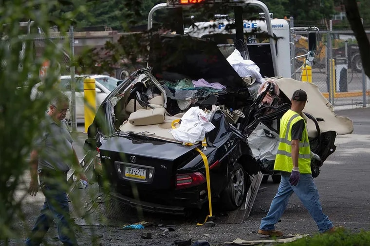 Investigators on the scene of the July 29, 2015 drag race crash that killed 3 dead and injured 1 on Sandmeyer Lane in Northeast Philadelphia. The car split in half after the impact with a tree.