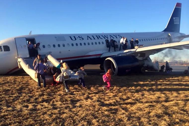 Passengers evacuate the US Airways plane on March 13, 2014, at Philadelphia International Airport.