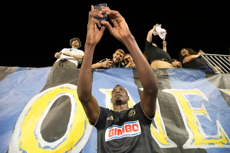 Union striker Cory Burke poses for a photo with some fans after a game earlier this season.