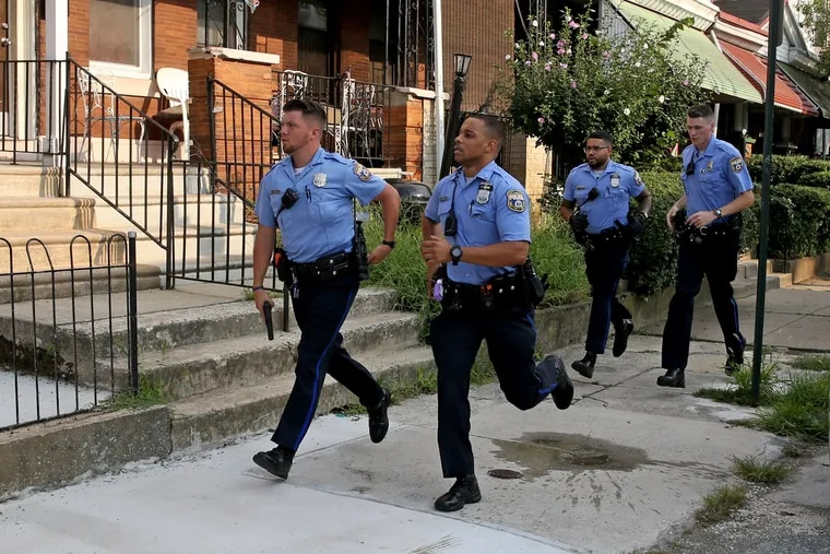 Police run to the scene at 15th Street and Erie Avenue Aug. 14, 2019,  after six police officers were shot in a confrontation with gunmen in the Tioga section of North Philadelphia.