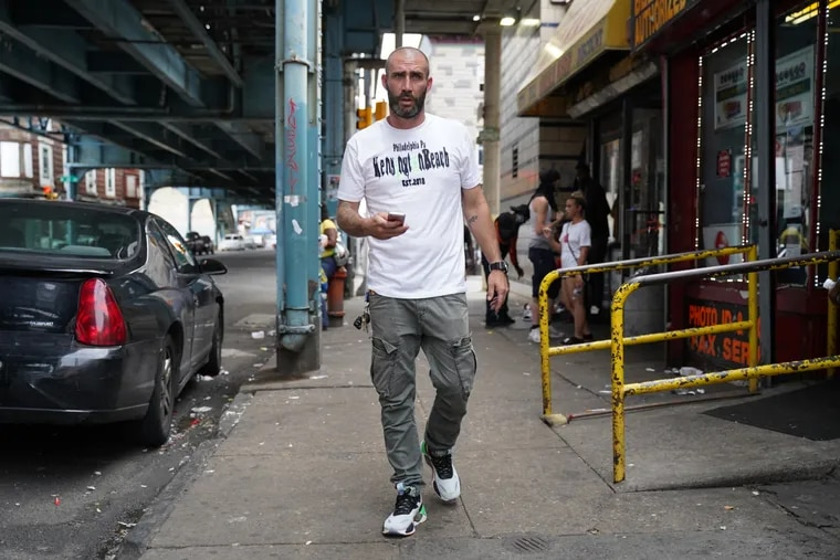 Mike Coyle, 37, at the intersections of Somerset Street and Kensington Avenue, walks with the iPhone he uses to document life around his Kensington neighborhood.
