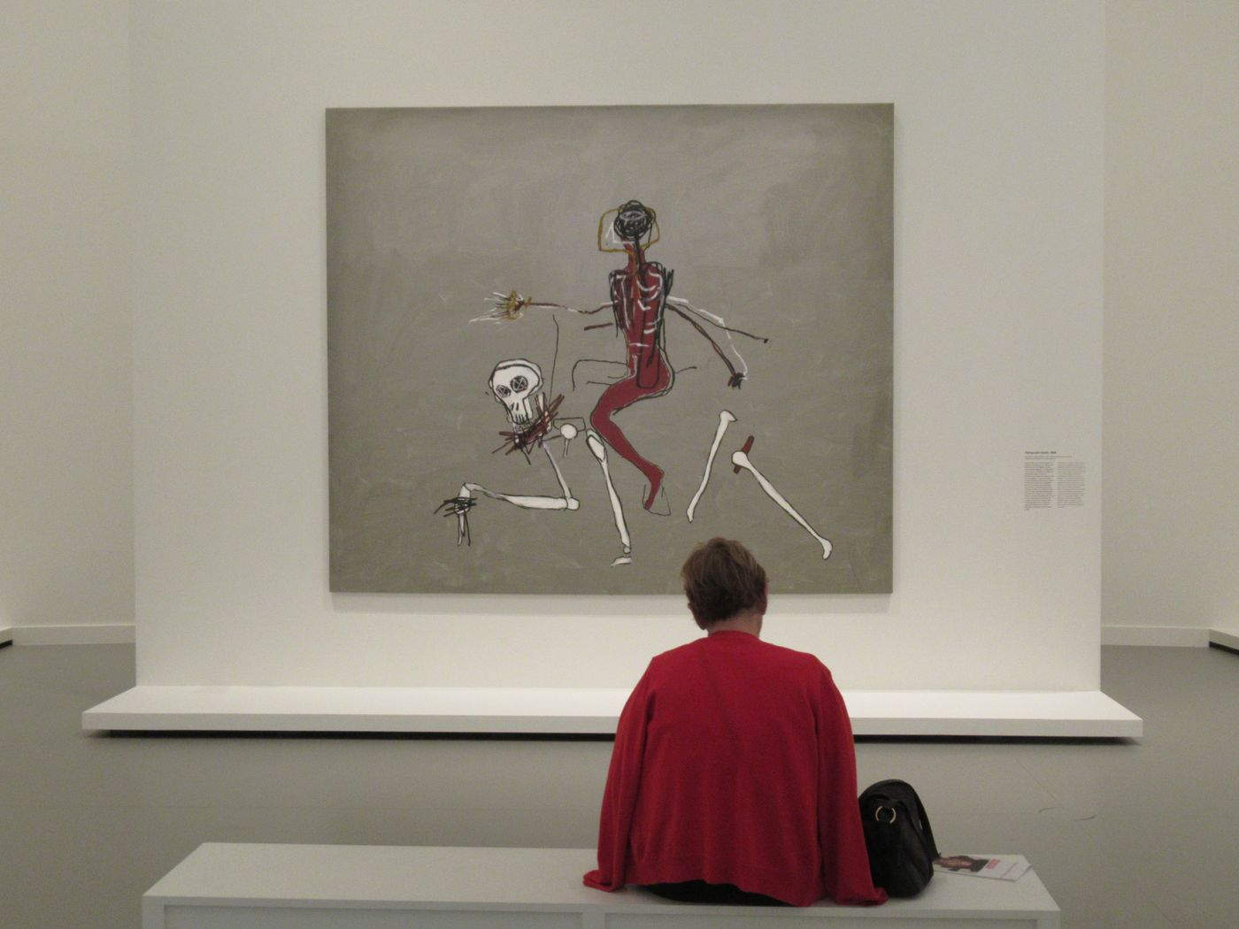 A visitor in front of Jean-Michel Basquiat's 'Riding with Death' in Paris, France on Oct. 4, 2018. To Dickinson professor Jerry Philogene, the painting reminds of the vodou spirit Baron Samedi.