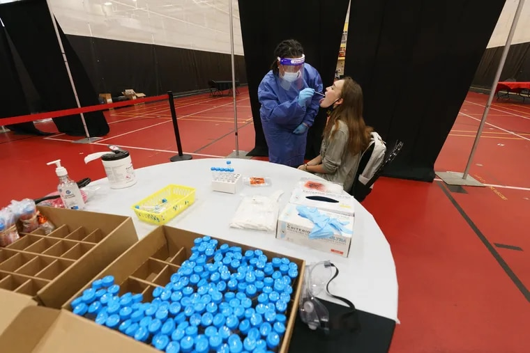 Registered Nurse Chantey White, left, administers a COVID19 test to Freshman Victoria Flint at Ursinus College where students are tested for coronavirus every week in Collegeville, PA.