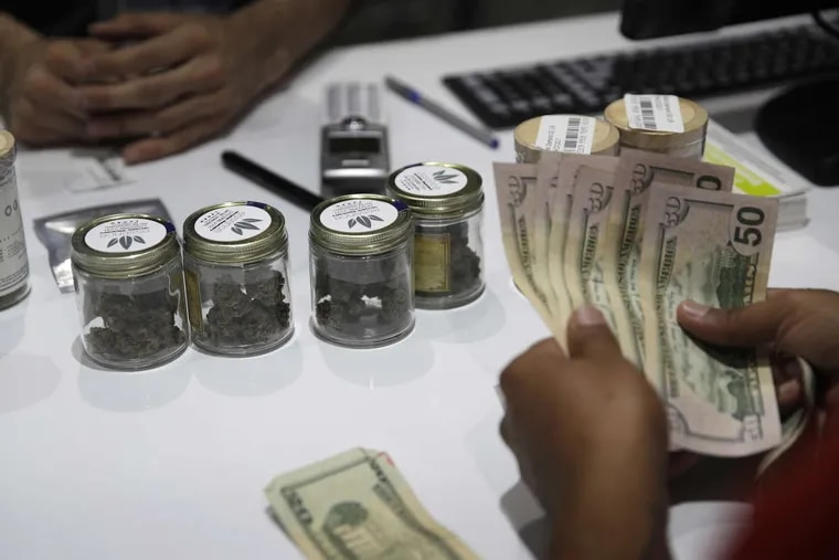 A person buys marijuana at the Essence cannabis dispensary in Las Vegas. Nevada dispensaries were legally allowed to sell recreational marijuana starting at 12:01 a.m. Saturday.