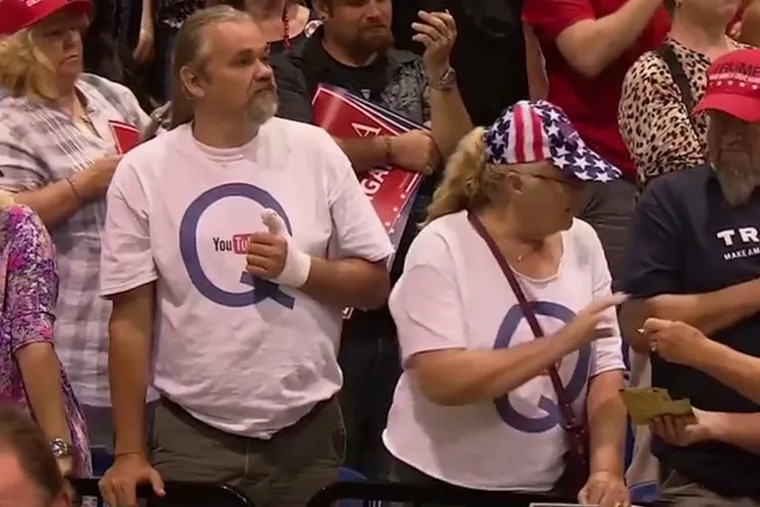 Two attendees to a rally held by President Trump Tuesday night wear shirts promoting one of the more bizarre conspiracy theories to emerge during his presidency.