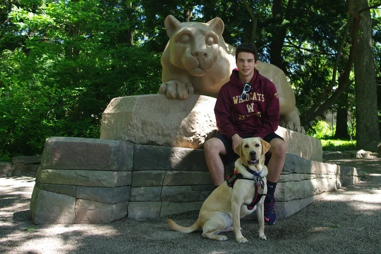 Nathan Reilly, 19, of Hatboro, with his diabetes alert dog, Fresca, at Penn State University.
