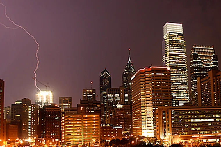 Last night's lightning storm, shown here in Center City, might have broken the extreme heat wave, but caused massive outages throughout the region. (Michael Perez / Inquirer)