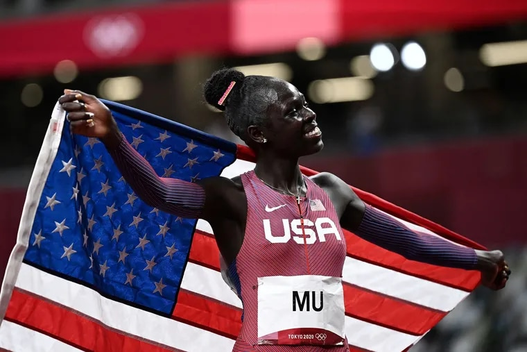 Athing Mu celebrates with an American flag after winning gold in the Olympics women's 800m final.