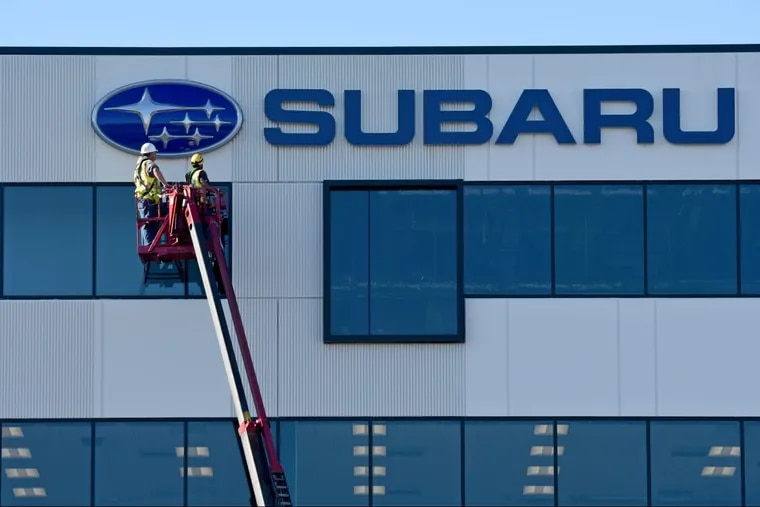 Mike Collins (left) and Frank Calabrese with Philadelphia Sign Co., of Palmyra, finish installing the Subaru logo and sign  at the automaker's still under construction U.S. headquarters in Camden's Gateway District.