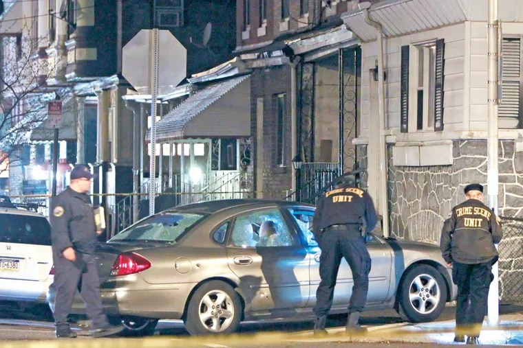 Investigators look over a suspect's car at the intersection of 51st Street and Willows Street in the Kingsessing section of Philadelphia, after police discharged their weapons wounding the driver.  For the Inquirer and Daily News/ Joseph Kaczmarek