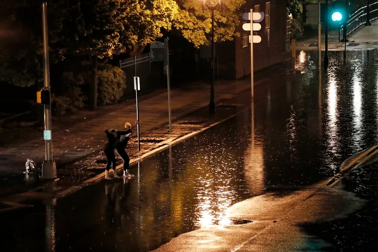 Two people jump into the high water at Delaware Avenue and Federal Street in Camden. They were caught in heavy rains in late May. More downpours are expected late Friday.