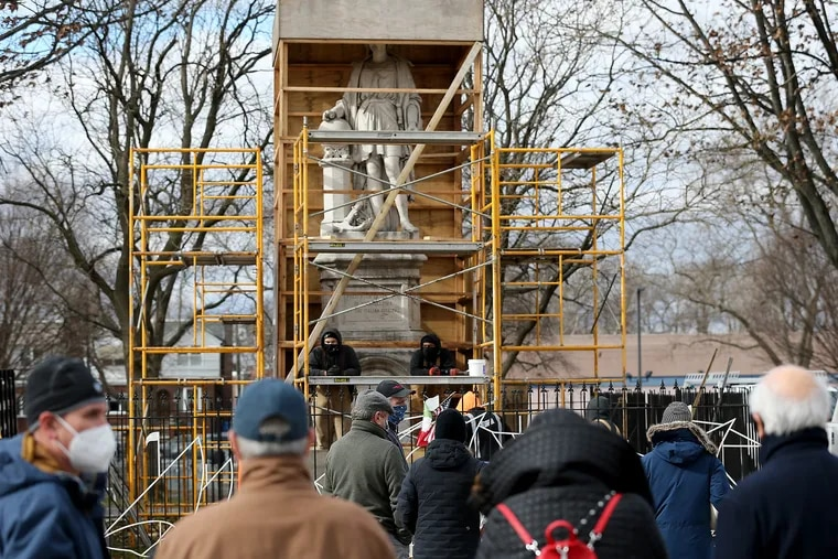 A team from Angelo's Marble & Granite Inc. inspect the condition of the Christopher Columbus statue in Marconi Plaza in Philadelphia on Jan. 27, 2021, when the box covering the statue was temporarily removed for the inspection.