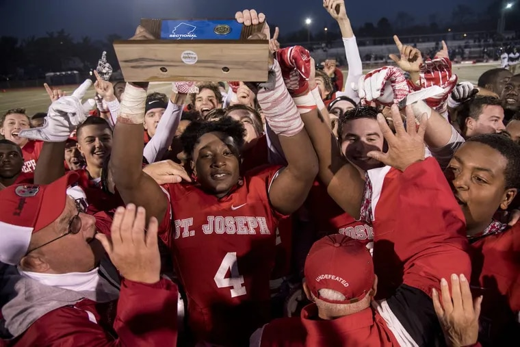 St. Joseph High's Qwahsin Townsel, surrounded by his teammates, holds up the championship trophy as the NonPublic Group 2 champs after they beat Mater Dei.