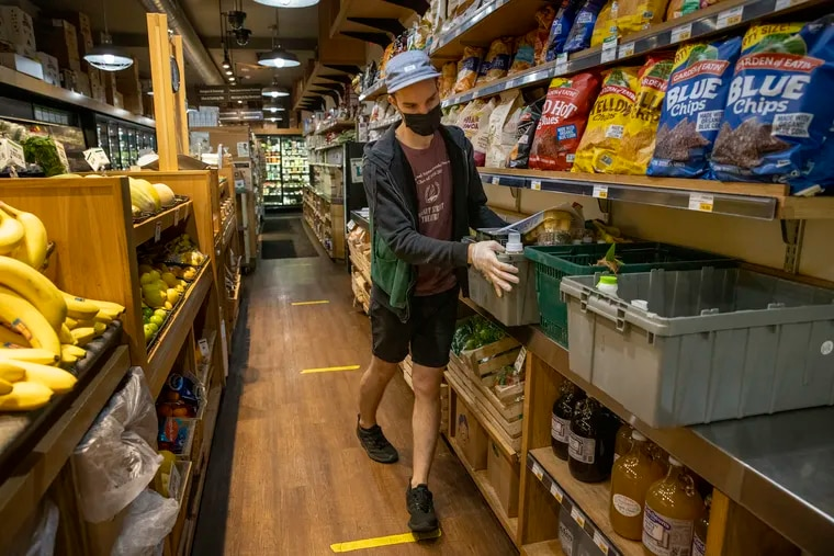 Grocery clerk Matt Sawyer organizes containers used to keep home-delivery and curbside pickup items together at Weavers Way Co-op in Philadelphia's Mount Airy section.