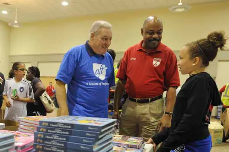 AFT-PA President Ted Kirsch (left) and PFT President Jerry Jordan talk with Mikalya McDonnell, a fifth grader at New Foundations Charter school, who was there with her mother, a third grade teacher, to pick up free text books handed out by the PFT and AFT at Steamfitters Local 420 in the Northeast in September 2013.