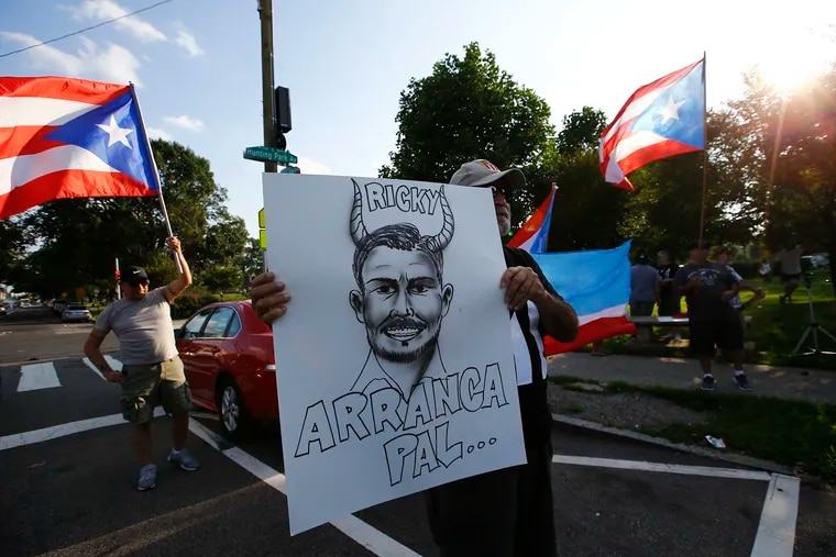 Ángel Medina holds a caricature of Puerto Rico Governor Ricardo Rosselló during a protest against the governor at Hunting Park on Friday, July 19, 2019.  The local Puerto Rican community gathered to protest against Puerto Rico Governor Ricardo Rosselló, after the leak of the 889 pages of group chat conversations that throw him into major crisis for racist, sexist and homophobic comments and allegations of corruption in his administration.