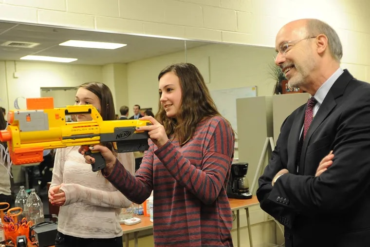 Gov. Tom Wolf, right, watches as Downingtown STEM Academy students, Julie Grier, left and Audrey Liebharolt, center, conduct a physics experiment during a tour of the facility Wednesday, March 4, 2015 in Downingtown, Pa. (Philadelphia Inquirer/Bradley C Bower)