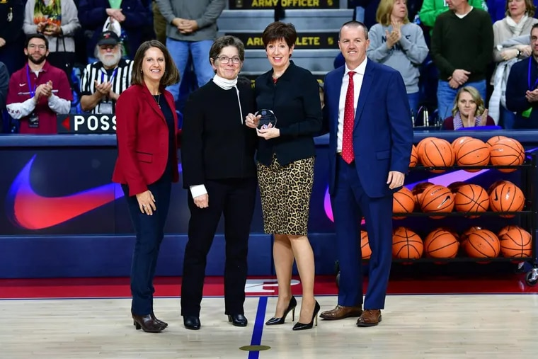 Penn athletic director Grace Calhoun (left) and women's basketball coach Mike McLaughlin (right) presented Notre Dame women's basketball head coach Muffet McGraw (center right) with a plaque celebrating the Philadelphia native's induction into the Naismith Basketball Hall of Fame. Next to McGraw is Mary DiStanislao, a former Penn athletic department administrator who was McGraw's predecessor as Fighting Irish head coach.
